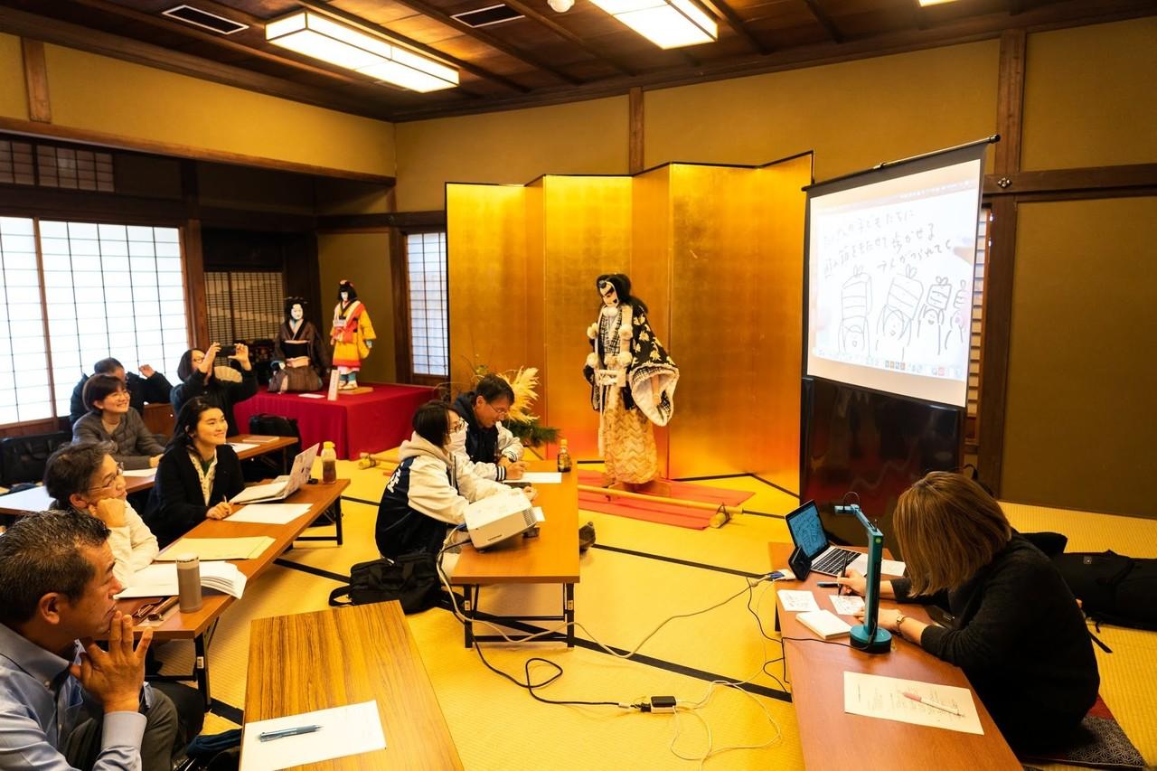 順番にアイデア出しをしているところ。右下のゲームマスター(中田)がアイデアをその場でポンチ絵に描き、書画カメラで投影。
